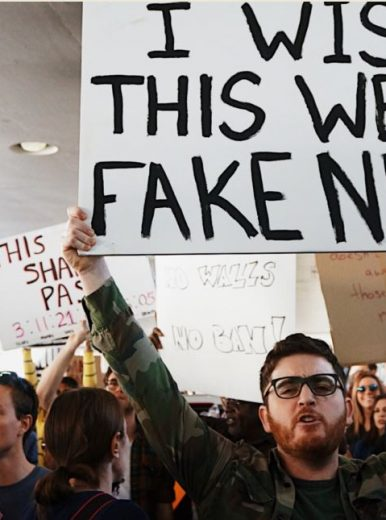 Man with fake news protest sign